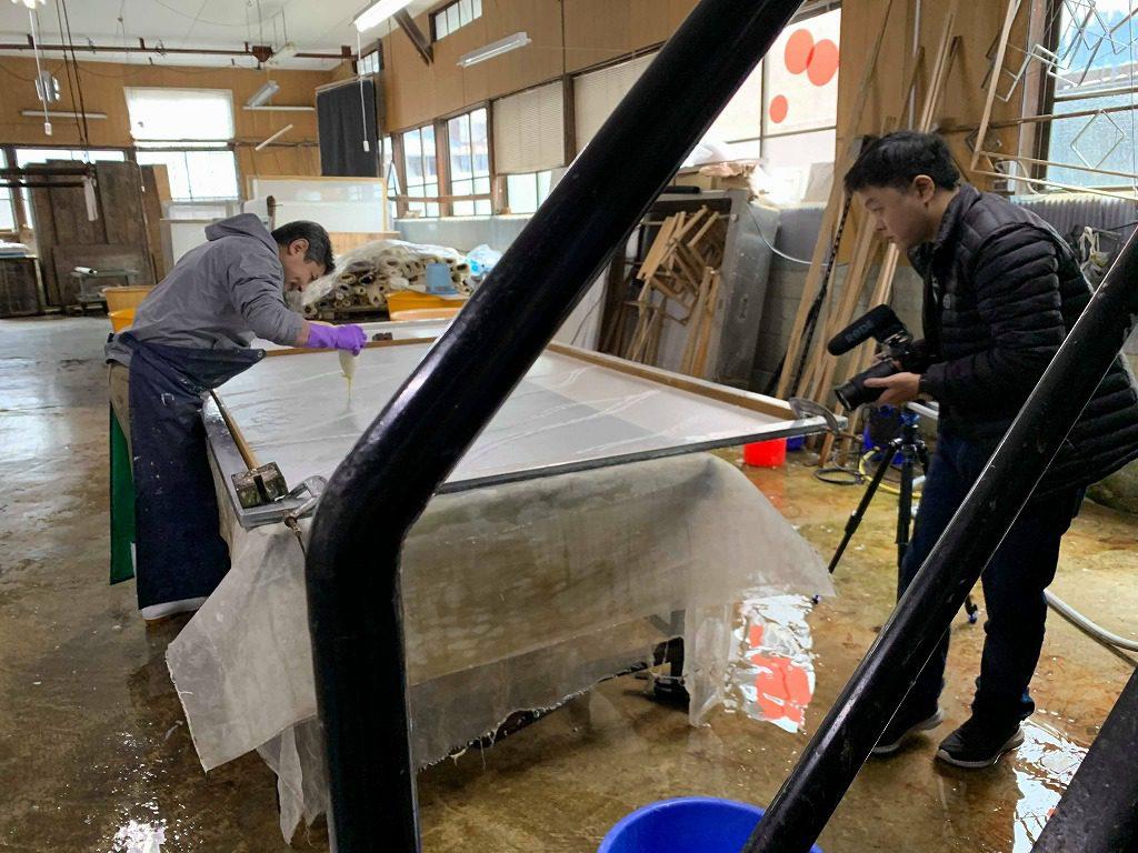 長田製紙所工場内にて、長田和也がオリジナル和紙を漉いています。